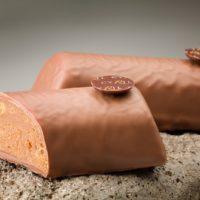 Praliné de avellana y almendra hojaldrado, cubierto de chocolate con leche. $6,10/100gr