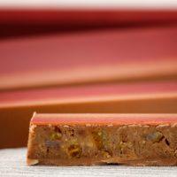 Barra de chocolate rellena de praliné crujiente de avellana con pedazos de naranja y limón enconfitados. $6,45/100gr