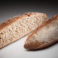 """Gran clásico de los panes franceses. Se elabora con 95% de harina integral y es un pan con alto contenido en fibras. Por lo cual es muy bueno para la saciedad y el tracto intestinal. Ideal para acompañar mariscos, salmón ahumado y ciertos quesos """"suaves"""". (Contiene solamente 0,7% de levadura.) $2,15"""