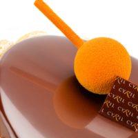 •Bizcocho de chocolate con base de mazapán •Bizcocho de limón •Compota de naranja amarga y maracuyá semi gelificada •Mousse ligera de praliné de avellana •Glaseado de chocolate negro Sugerencia: sacar quince minutos antes de servir.