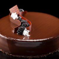 •Bizcocho de chocolate Sacher mojado con almíbar de mora •Mermelada de mora •Ganache de chocolate negro 58% de cacao •Glaseado de chocolate negro Sugerencia: sacar del frío cuarenta minutos antes de servir.