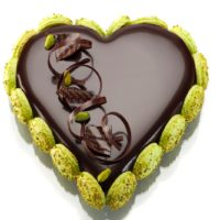 Bizcocho de chocolate con base de mazapán Suprema de pistacho Mousse de chocolate Glaseado de chocolate Macarrones. Sugerencia: sacar del frío media hora antes de servir. Disponible a la venta solamente el domingo 12 de mayo. 6/8 Personas: $26,45 8/10 Personas: $32,85