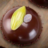 Bizcocho de chocolate con base de mazapán Crème prise de pistacho Mousse de chocolate negro con base de masa bomba Glaseado de chocolate. Sugerencia: sacar del frío veinte minutos antes de consumir. $4,75