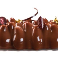 Bizcocho de chocolate con base de mazapán Suprema de avellana Mousse de chocolate negro Crujiente de praliné de avellana Glaseado de chocolate. Recomendación del Chef Cyril, sacar del refrigerador una hora antes de consumir.