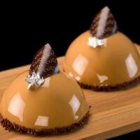 """-Bizcocho de miel y nuez -Manzanas al caramelo manera Tarte Tatin -Crème diplomate de caramelo -Glaseado """"caramel or"""" Recomendación del Chef Cyril, sacar del refrigerador diez minutos antes de consumir. $4,65"""
