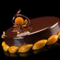 -Bizcocho de mandarina -Bizcocho de chocolate con base de mazapán -Crème brûlée perfumada con ralladura de mandarina -Mousse de chocolate -Glaseado de chocolate. Recomendación del Chef Cyril, sacar del refrigerador una hora antes de consumir.